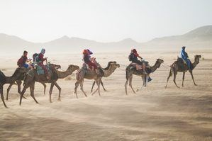 People on camels riding across desert sand storm starting
